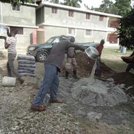 De werklui van de aannemer zeven grint voor de beton.