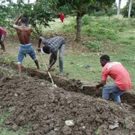 Een ploeg jonge mannen graaft de greppel voor de leidingen naar Sent An.